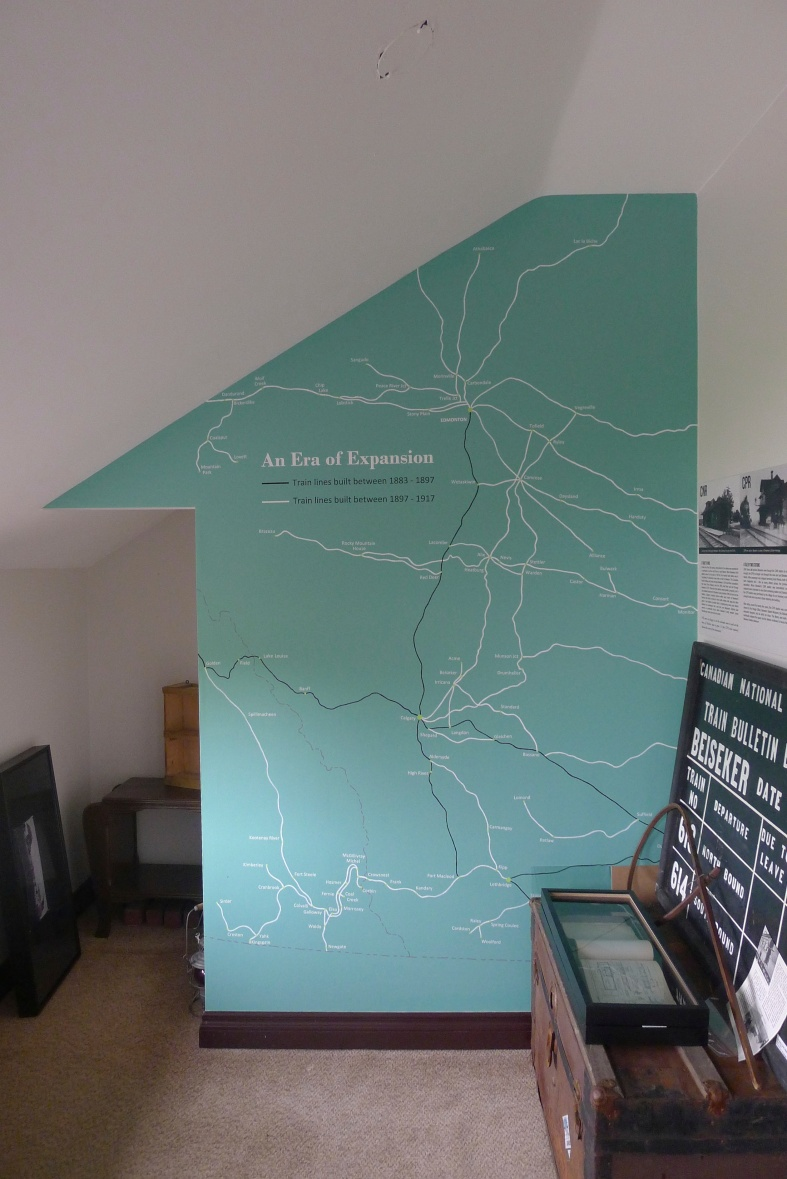 I painted a train map on the wall (with the help of a projector) and used vinyl decals to label towns.
