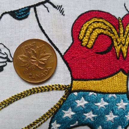 The red bodice and yellow belt were filled with chain stitch; the 'W' was worked with hungarian and plain braided chain stitch then outlined in black couching; the stars on the shorts were done with a combination of fly and straight stitch on a background of blue stem stitch; the Lasso of Truth was done by winding yellow thread through black backstitch.